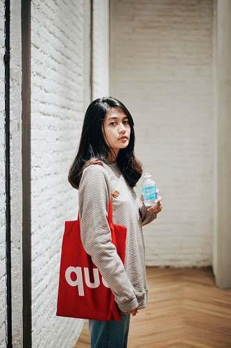 human woman wearing grey shirt with Supreme tote bag people