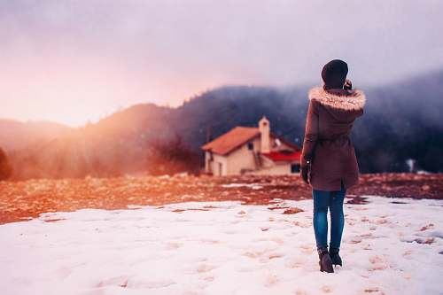 human woman wearing parka hoodie standing in front of house people