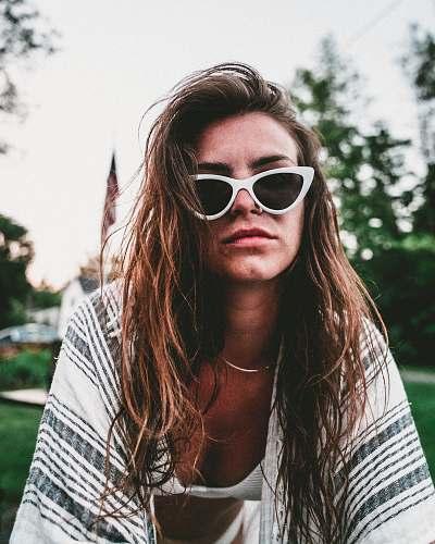 human women's black lens sunglasses and white bra people