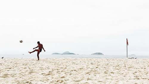 clothing man playing soccer on beach shorts