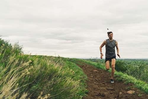 clothing man wearing gray tank top running during daytime shorts