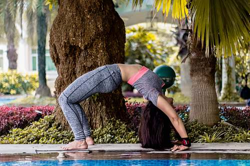 clothing woman doing stretching exercise near swimming pool helmet