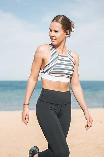 clothing woman wearing sports bra walking on seashore footwear