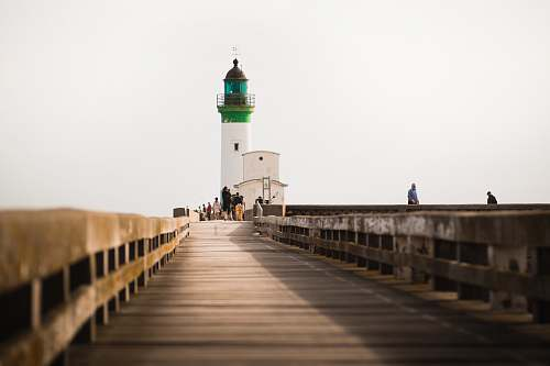 building person standing white and green lighthouse lighthouse