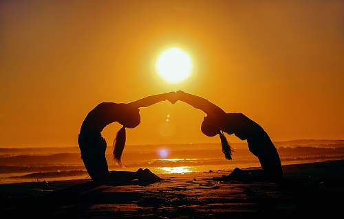 morocco silhouette of two woman bending while holding hands during sunset yoga