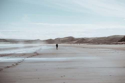 ocean person running on desert grey