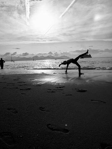 nature grayscale photography of person bending on shore during daytime ocean
