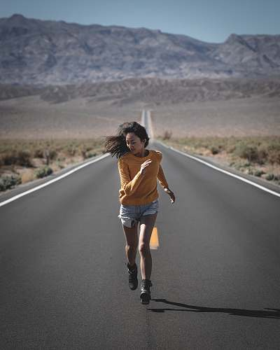 apparel woman running on road during daytime shorts