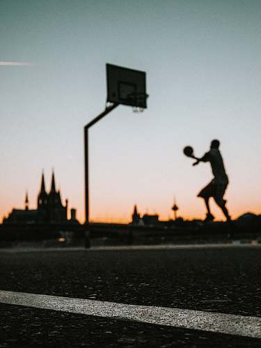 germany man holding ball jumping near portable basketball hoop silhouette