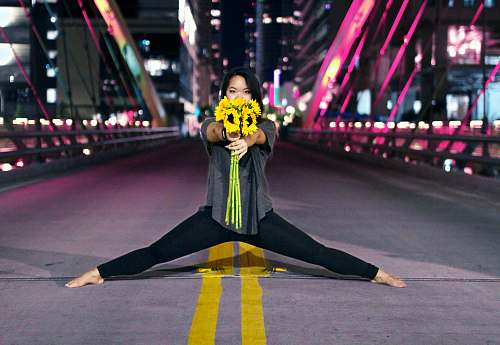 dance pose woman holding sunflowers while splitting at the center of road during nighttime leisure activities