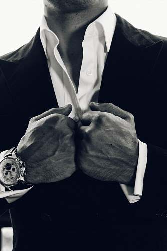 suit grayscale photography of man's suit wristwatch