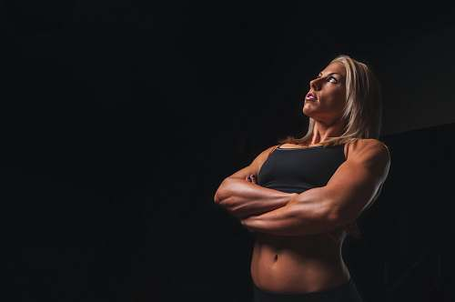 sports body builder woman wearing black crop-top cross armed closeup photography female
