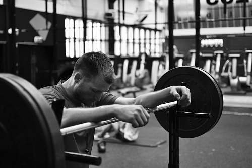 gym gray scale photo of man sitting on bench press black-and-white