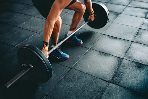 gym person holding black barbell footwear