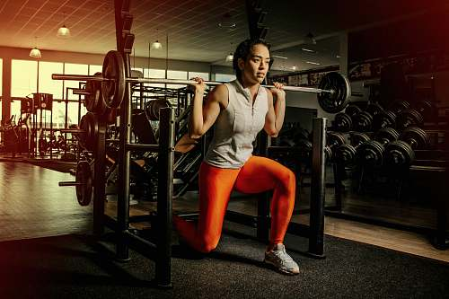 exercise woman wearing gray shirt and orange leggings working out