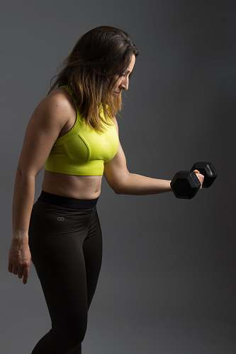 human woman wearing pink sports bra holding dumbbells person