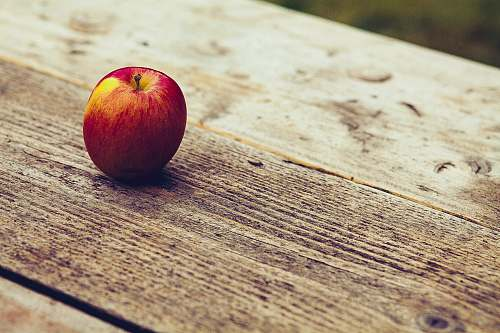 plant red apple on brown surface fruit