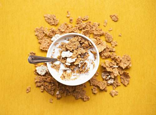 yellow top view of corn flakes in bowl with milk and silver spoon cereal
