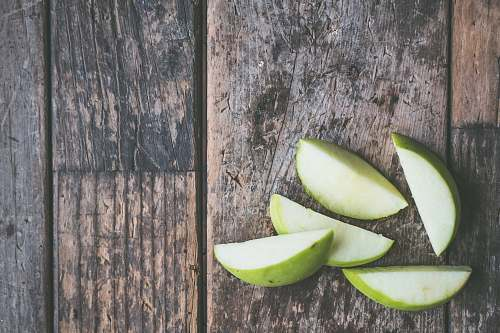 food five green apple slices on brown wooden panel apple