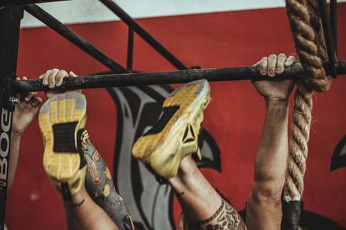 brazil person wearing yellow-and-black Reebok low-top athletic shoes hanging on pull-up bar workout