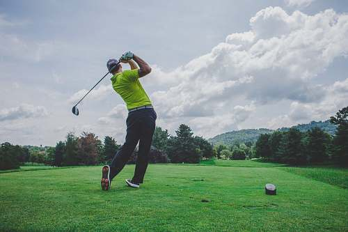 sports photo of man swinging golf driver sport