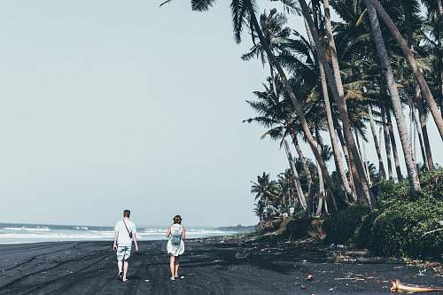 nature man and woman standing on the seashore coast