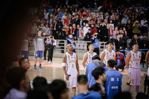 person four basketball players forming a line while standing on court surrounded by crowd people