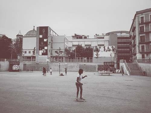 people girl ride on skateboard near building grey