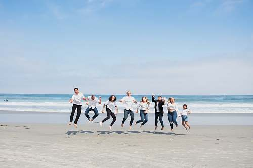 person group of people jumping on seashore people