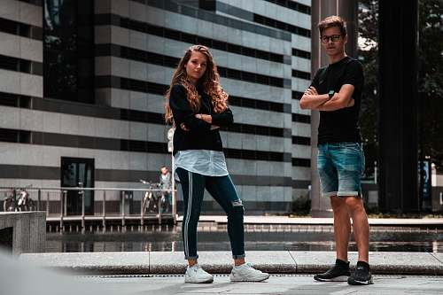 apparel man and woman standing near building clothing