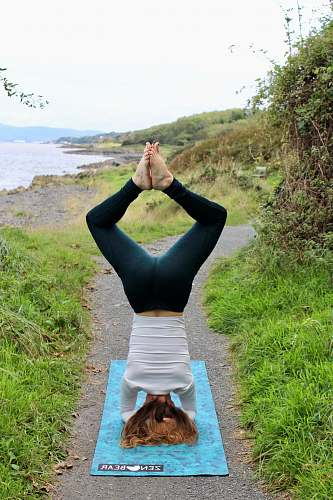 person man doing headstand on teal textile on pathway on island working out