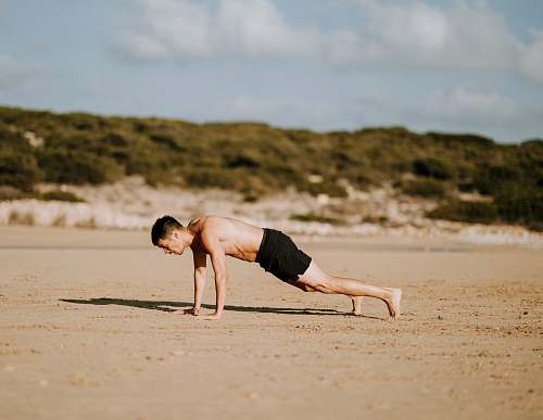 person man doing push up on sand people