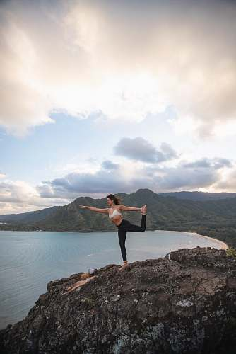 person man doing yoga on rock formation outdoors