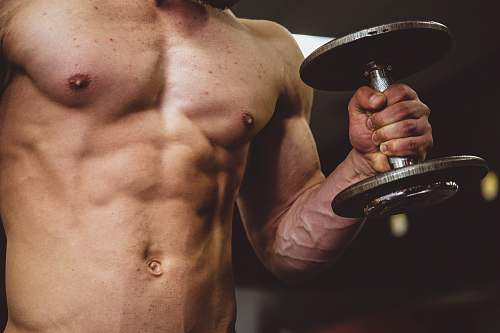 person man holding black dumbbell people