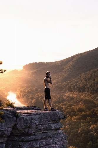 people man in black shorts standing on cliff during golden hour person