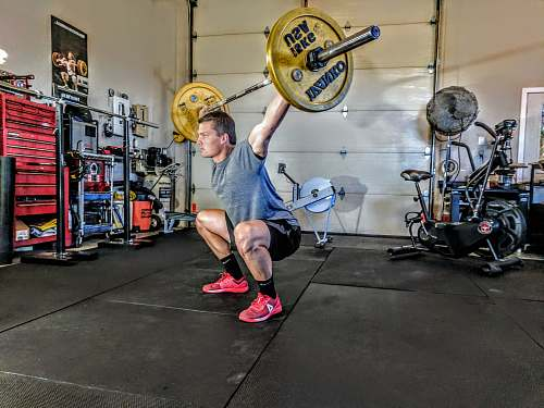 people man in gray t-shirt lifting gray and yellow barbell person