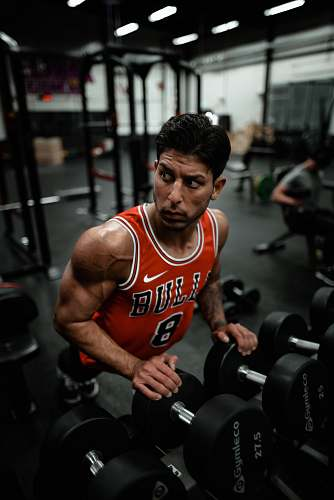 person man in red Chicago Bulls jersey doing push-up exercise on dumbbells sports
