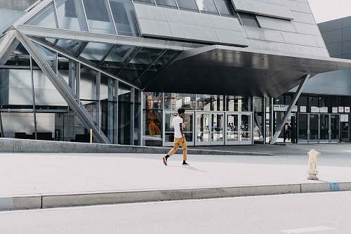 person man in white t-shirt walking beside building during daytime architecture