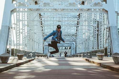 person man jumping on grey and white bridge during daytime people