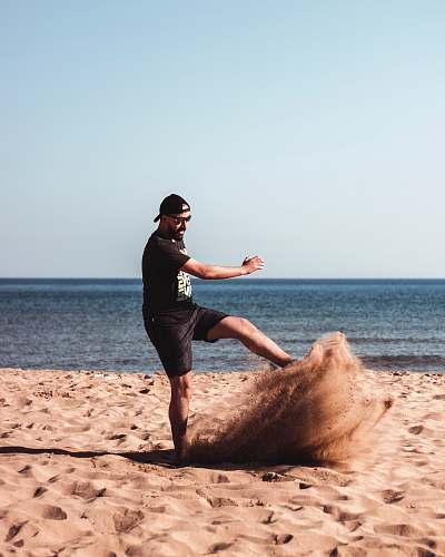 person man kicking a sand beside seashore during daytime nature