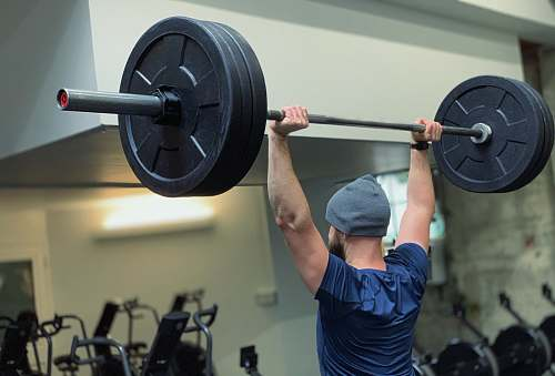 sports man lifting barbell in gym person