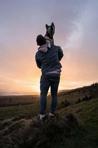 person man lifting dog during sunset nature