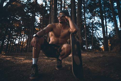 person man sitting on the air leaning on the surfboard on forest clothing