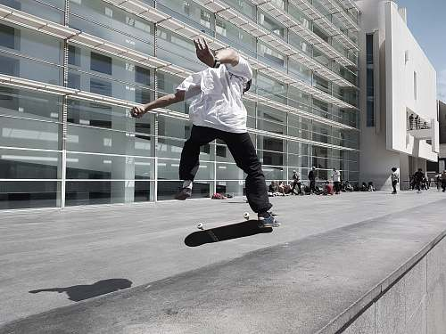 person man skateboarding beside building during daytime people