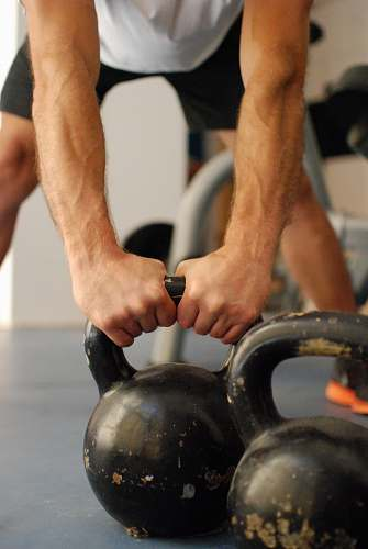 person man standing and holding kettle bell finger