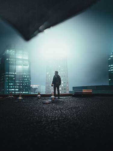 person man standing on roof top at night asphalt