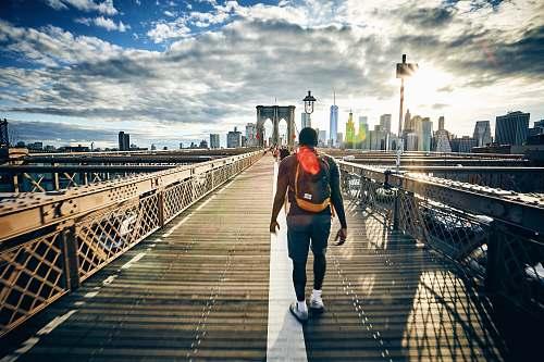 person man walking on bridge people
