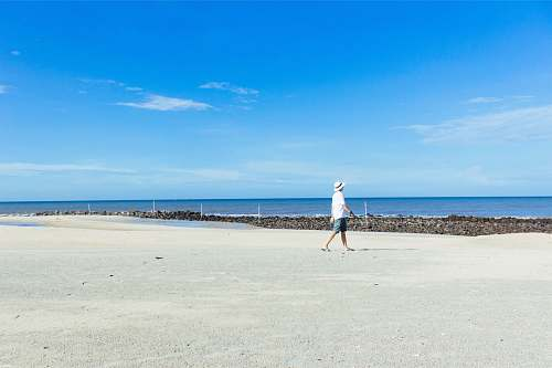 person man walking on seashore under blue sky nature