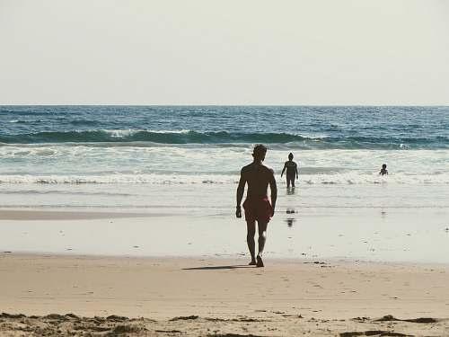 person man walking towards shore during daytime people