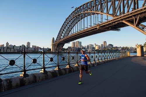 person man wearing blue tank top running under bridge building